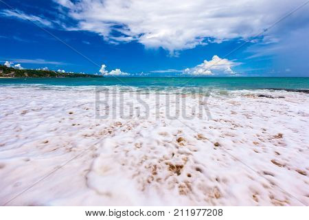 Sea white foam on the sand closeup in sunny weather with a blue sky and large white clouds. Dreamland Beach New, South Kuta, Bali, Indonesia.