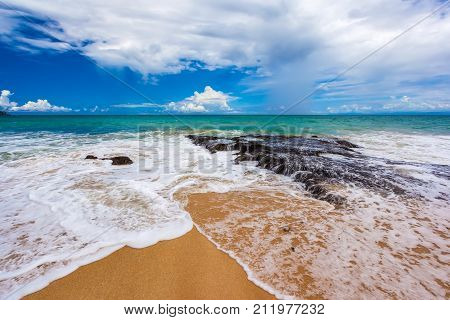 A sea wave separates in the middle forming a white foam in sunny weather with a blue colorful sky and bright white clouds. Dreamland Beach New, South Kuta, Bali, Indonesia.