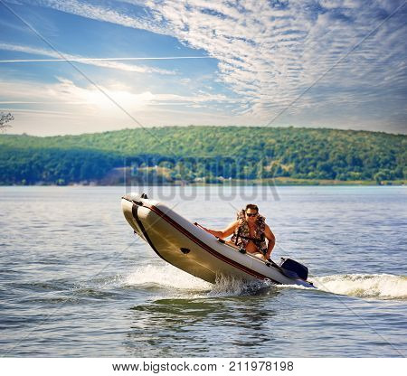 Inflatable motor boat with man in life jacket against the backdrop of green beach. Summer landscape. The concept of movement and freedom.