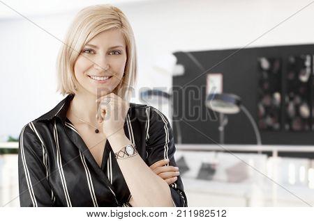 Businesswoman Portrait. Mid adult businesswoman at office, happy, smiling.