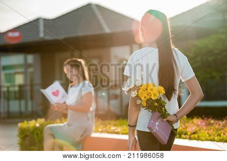 The girl which is the daughter flower and gift box is hidden behind her to bring it to her mother who is sitting reading in mother's Day greeting cards.
