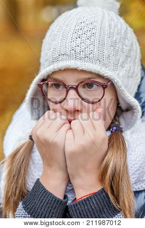 portrait of teenage girl in glasses, blowing on her hands to keep warm in the cold