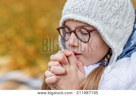 close portrait of a little beautiful cute girl teenager with glasses and cozy scarf praying makes a wish