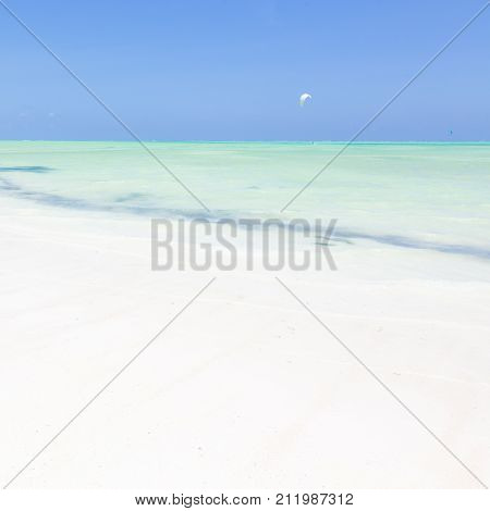 Solitary kite surfer kite surfing on picture perfect white sandy beach with turquoise blue sea, Paje, Zanzibar, Tanzania. Copy space.