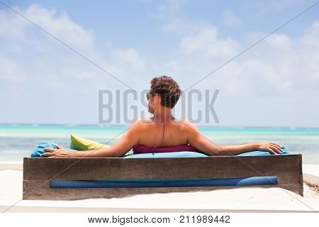 Relaxed man in luxury lounger enjoying summer vacations on beautiful beach. Guy feeling free, relaxed and happy. Concept of vacations, freedom, happiness, enjoyment and well being.