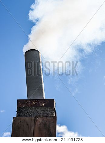 Improvised chimney made from scrap parts producing smoke.