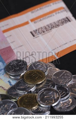 Illustration for Spending money for holiday and payment for travel, boarding pass in isolated black focused at coins/money