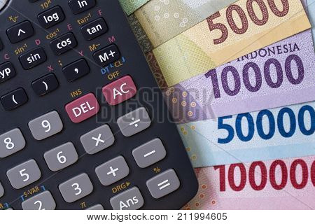 Top view / Flat Lay of Spending money and payments calculation illustrated with banknotes, and calculator