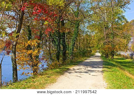 A trail along Potomac River in Harpers Ferry National Historic Park West Virginia USA. Colorful deciduous trees in fall on the along the river bank.