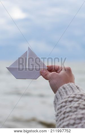 Close-up of human hand paper boat sea vague backround