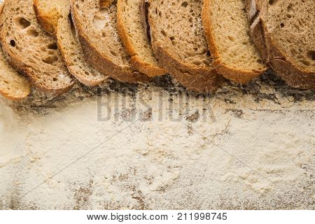 Sliced pieces of bread on the top of wooden table with flour, free space for text.  Flour as a main ingredient for cooking homemade bread.