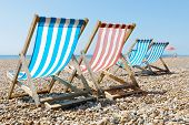 Colorful empty red and blue deckchairs and a parasol on the beach poster