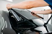Male specialist with car tinting film in hands poster