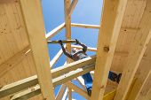 Carpenter roofer at work with wooden roof construction. poster