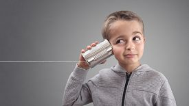 Boy on tin can phone listening to curious good news