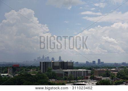 A Hazy Skyline View Of Atlanta, Georgia On A Bright Sunny Day With Big Puffy Clouds.