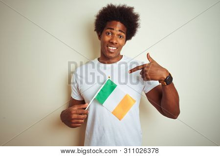 Young african american man holding Ireland Irish flag standing over isolated white background with surprise face pointing finger to himself