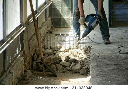 A Man Using A Perforator Dismantles The Cement Floor In A Room With Large Windows. Daylight.