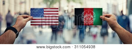 Two Hands Holding Different Flags, Us Vs Afghanistan On Politics Arena Over Crowded Street Backgroun