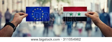 Two Hands Holding Different Flags, Eu Vs Syria On Politics Arena Over Crowded Street Background. Dip