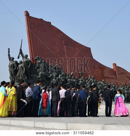 Pyongyang, North Korea - May 1, 2019: Local People Near Mansudae Monument. Is The Most Respected Mon
