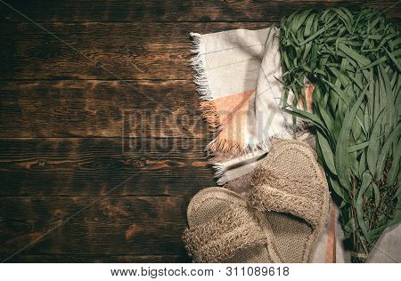 Eucalyptus bath broom, bath slippers and a towel on a bathhouse table flat lay background with copy space. poster