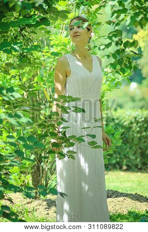 Young Beautiful Girl In A White Dress Close-up On The Background Of Green Bushes With Flowering Jasm