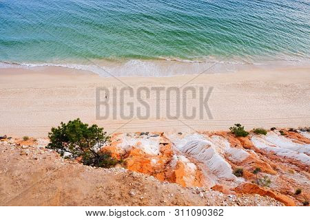 Aerial view on the beach Praia da Falesia Barranco das Belharucas with red rocks, golden sand and green ocean waves. Region Faro, Algarve. Vacation in Portugal. Beautiful seascape. Space for text. poster