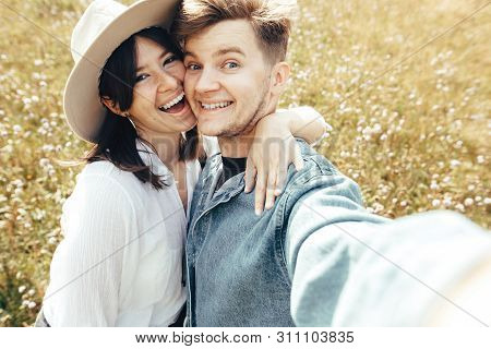 Happy Hipster Couple Making Selfie And Smiling In Sunny Mountains. Stylish Young Family Taking Photo