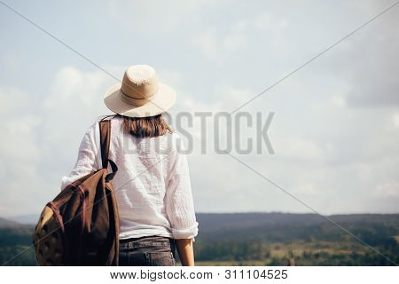 Hipster Girl With Backpack Traveling And Standing On Top Of Sunny Mountain And Looking At Sky And Wo