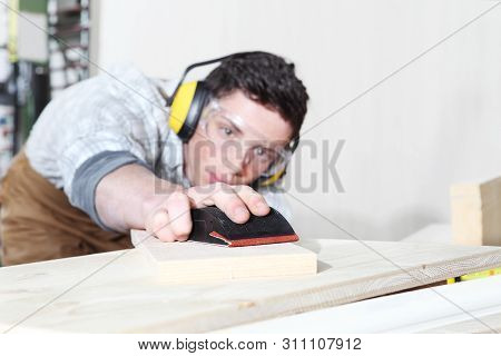 carpenter man work in the carpentry, sanding wooden boards with sandpaper, protected with ear muffs and glasses poster