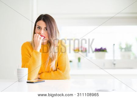 Young beautiful woman drinking a cup of coffee at home looking stressed and nervous with hands on mouth biting nails. Anxiety problem.
