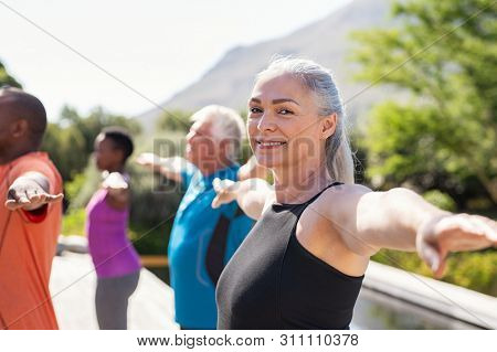 Portrait of happy senior woman practicing yoga outdoor with fitness class. Beautiful mature woman stretching her arms and looking at camera. Portrait of smiling lady with outstretched arms at park.