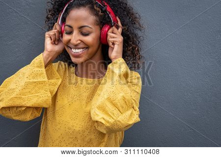 African girl listening to music with her wireless headphones while leaning against grey wall. Happy beautiful young woman listening music with closed eyes enjoying the melody on gray background.