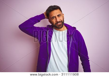 Young indian man wearing purple sweatshirt standing over isolated pink background confuse and wonder about question. Uncertain with doubt, thinking with hand on head. Pensive concept.
