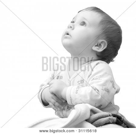 Baby girl with hands clasped together and looking up. Isolated on white