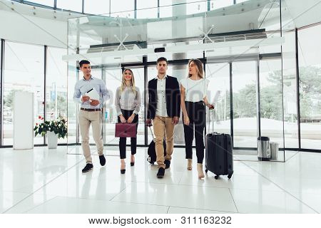 Business People Talk And Walk Together With Digital Tablet Tablet And Luggage.