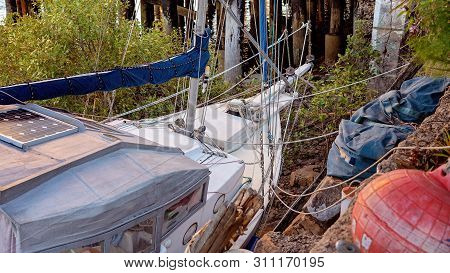 A Decrepit Old Wooden Boat Abandoned In A State Of Disrepair Run Ashore On A Mangrove River Bank