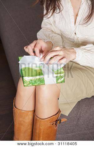 opening green present sitting on sofa