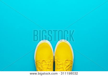 Minimalist Photo Of Yellow Sneakers With Tied Shoelaces. Flat Lay Image Of Yellow Summer Footwear. P
