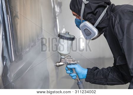 A Male Worker In Jumpsuit And Blue Gloves Paints With A Spray Gun A Side Part Of The Car Body In Bla