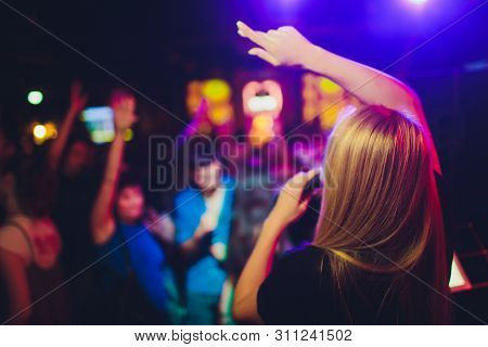 Beauty Model Girl Singer With A Microphone Singing And Dancing Over Holiday Glowing Background. Kara