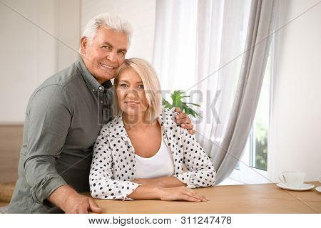 Portrait of affectionate senior couple at home. Space for text poster