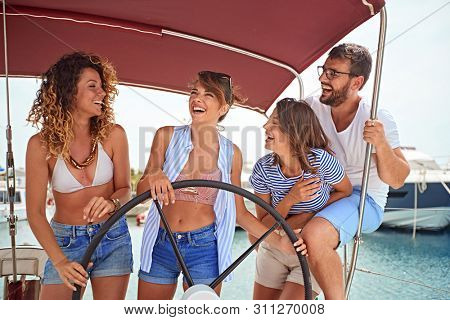 Smiling man sailing on yacht with happy girl's friends