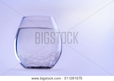 A Glass Of Cold Fresh Water. A Glass With A Cracked Glass, Copy Space.