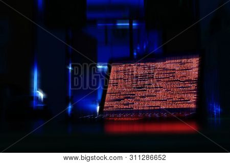 Computer Laptop In A Dark Room. Computer Displaying Red Code Meaning Problem, Error, Hacker Or Virus