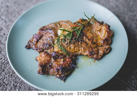 The Picture Of Round Plate With Grilled Beef Steak And Rosemary