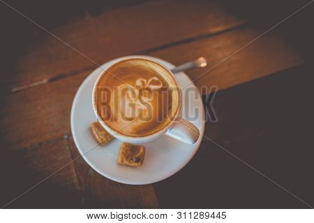 Picture Of Latte Hot Coffee With Foam Milk Art On A Wooden Table