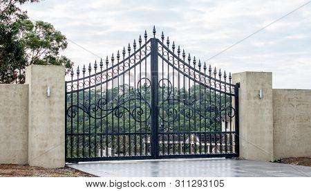Black Metal Wrought Iron Driveway Property Entrance Gates Set In Concrete Brick Fence, Lights, Garde