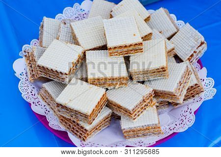Waffles With Condensed Milk. Sweet Dessert. Waffles In A Plate Frisky Pieces On A Blue Background. E